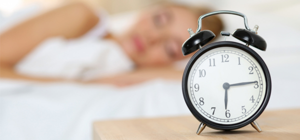 Image of a woman asleep with an alarm clock oversleeping