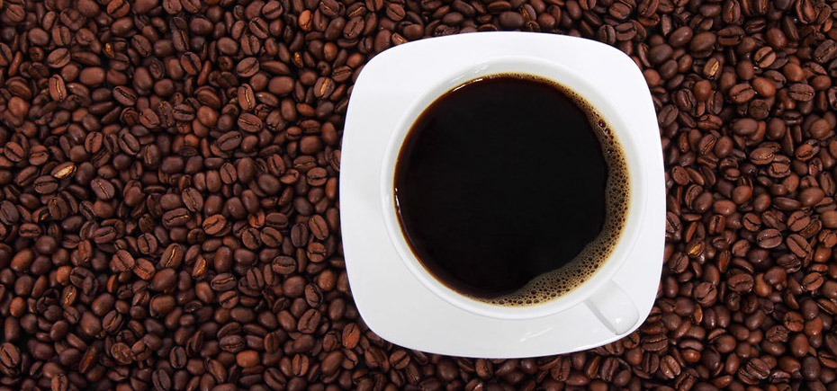 Image of a cup of coffee sat on a pile of coffee beans